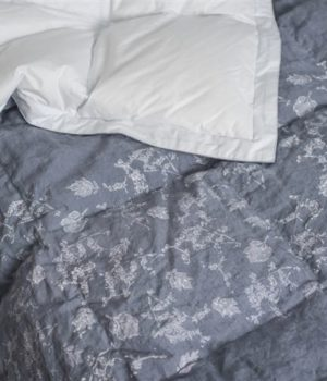 A dark gray duvet, with off-white floral accents and white underside exposed laid out on bed.