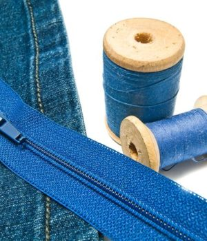 denim with zipper and spools of thread on white background